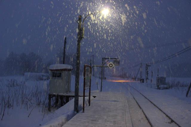 吹雪の中、駅と踏切の灯りが印象的な真冬の糠南駅
