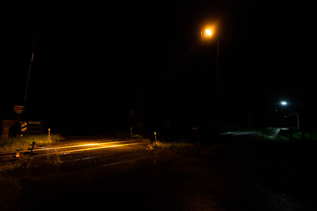 雨上がりの宵闇の中に浮かぶ中問寒糠南線踏切と糠南駅