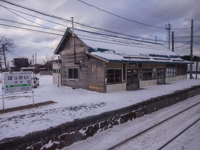 無彩色の情景の中に静かに佇む抜海駅を車窓に見送る