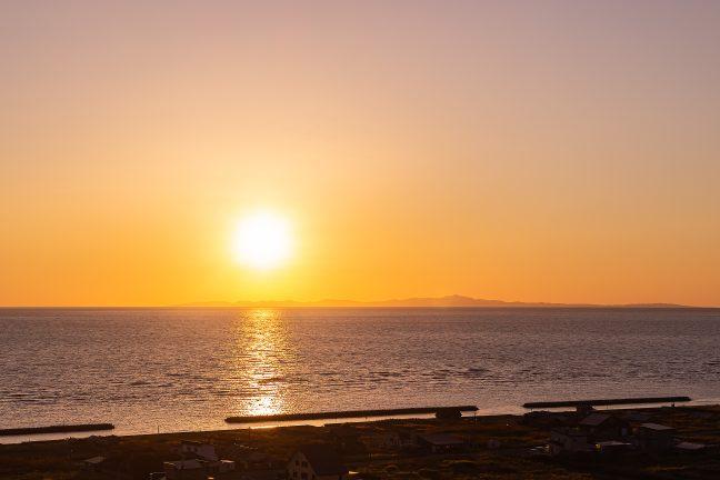 夕景の利尻水道に低く横たわるのは礼文島