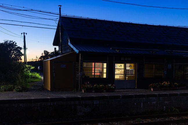 残照をバックに、駅舎と駅前通りを眺める