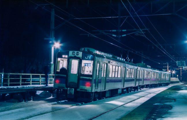 夜の津軽湯の沢駅に停車する秋田行きの普通列車