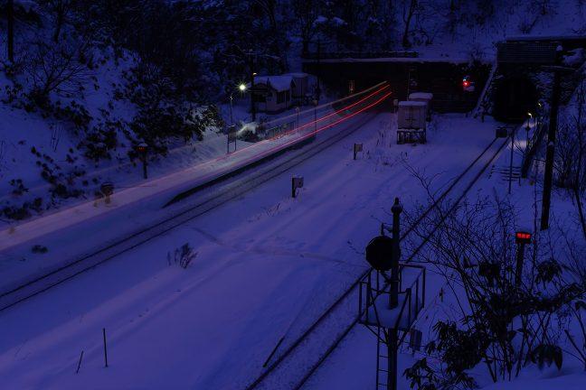 夜明け前の小幌駅を貨物列車が通過していく