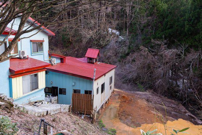 津軽の名湯・古遠部温泉裏の河畔には、赤褐色の温泉成分が析出している