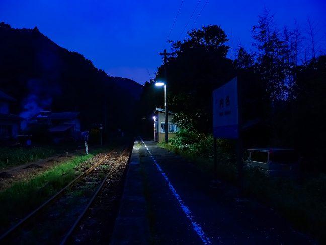 駅前に1軒だけある民家の敷地から焚き火の煙が立ち昇る夕暮れ