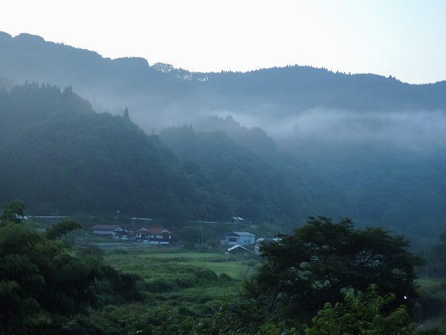 低い丘陵に囲まれた谷間に民家が点在する内名の集落が遠くに見える