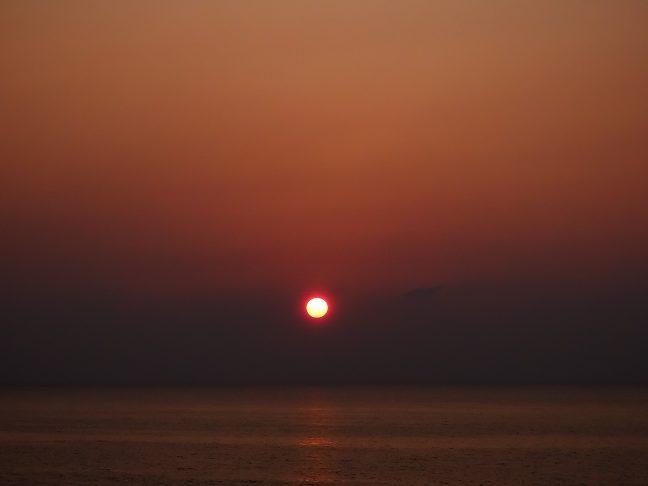 遮るもののない海原に夏の夕日が沈んでいく