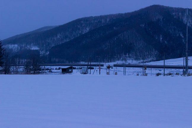 少し離れたところから、雪原に埋もれる駅を遠望する