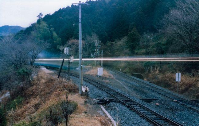 ライトの軌跡と排煙を残して普通列車が出発していく
