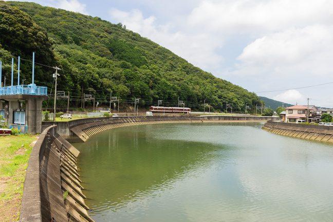賀茂川沿いの岸壁に沿った単線を走ってくる普通列車