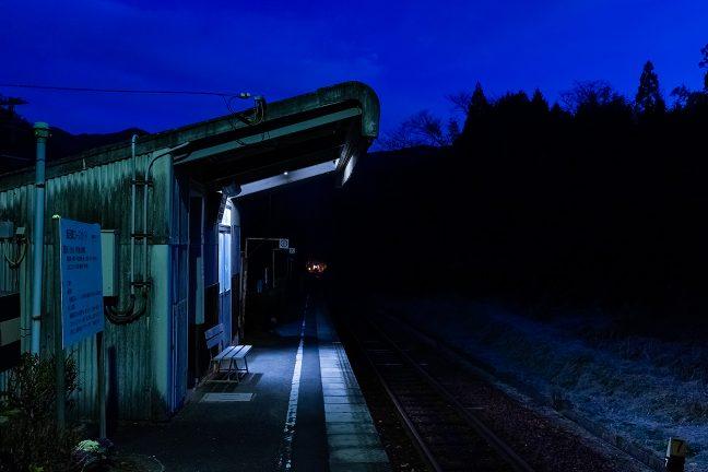 山間部にエンジン音を響かせながら遠ざかる始発列車の後ろ姿