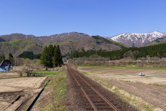 羽後長戸呂駅のホームから、長閑な山里と残雪をまとった大石岳を眺める