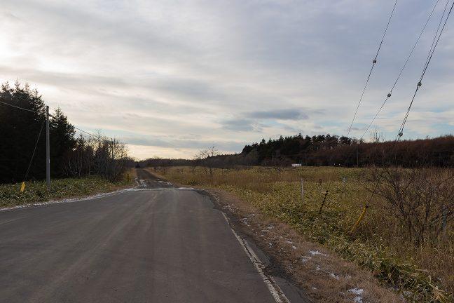 道道は駅の南で東から南に直角に折れており、線路に並行する西向きの道は未舗装となる