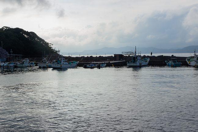 漁船が係留され波止場に釣り人の姿が見える長閑な風景