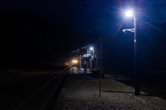 レールにヘッドライトのきらめきを落として到着した始発列車