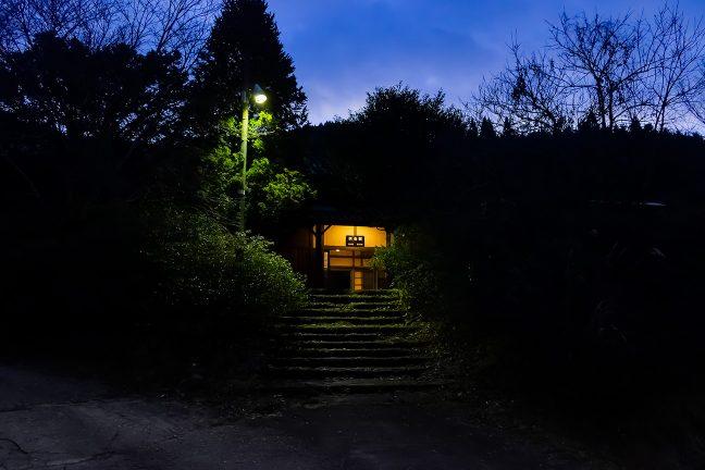 取り付き道路から通じる階段越しに眺めた矢岳駅舎