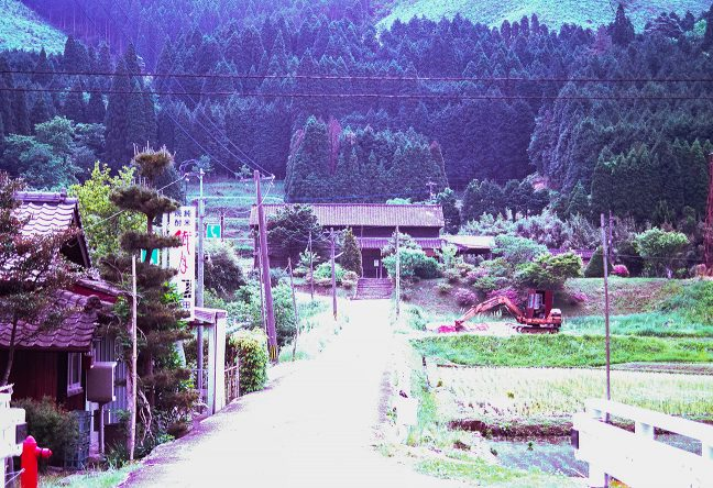 集落に通じる取り付き道路から眺めた矢岳駅舎