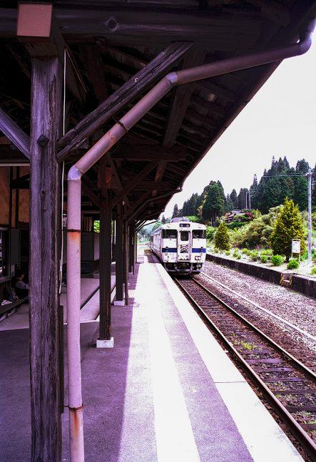 ヘッドマークを掲げた観光仕様の普通列車で駅を後にする