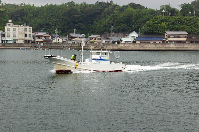 狭い水道を行く漁船