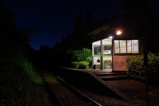 微かに残照を残す夜空の下、静かに佇む久我原駅