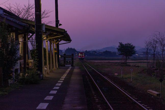 ディーゼルエンジンの排気とテールライトの軌跡を残して走り去る列車を見送る