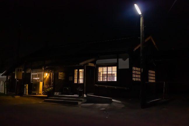 窓から漏れる明かりが温もりを感じさせる法華口駅の夜